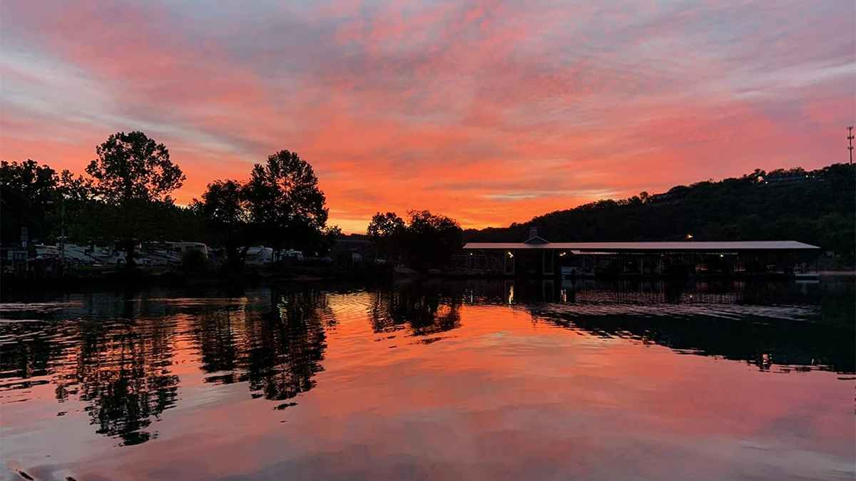 sunset over Lake taneycomo with two people fishing at sunset in Branson, Missouri, USA