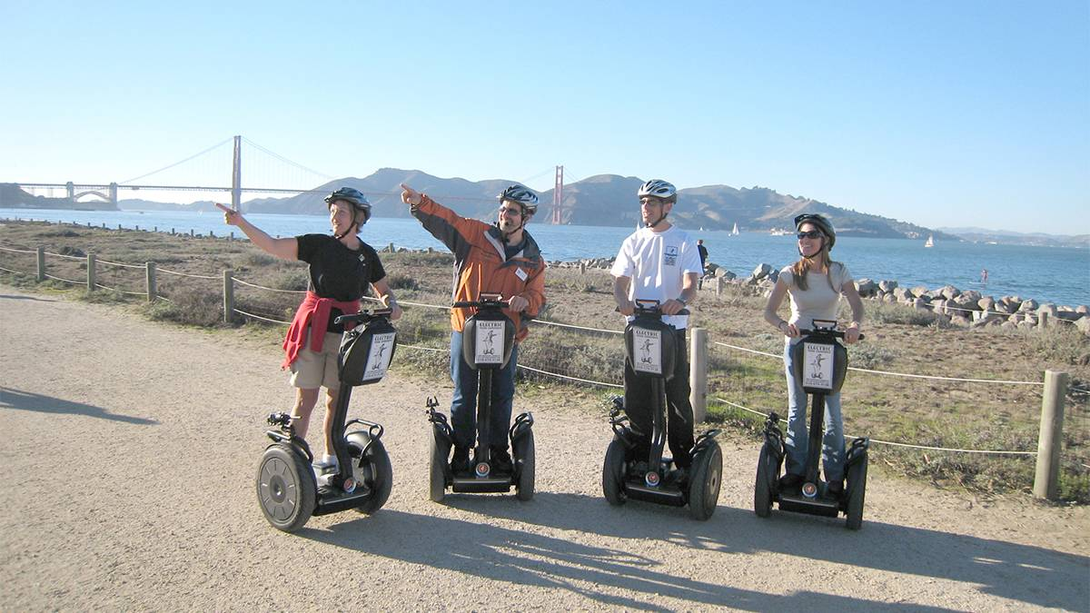 four people on segways standing in front of the Golden Gate Bridge in San Francisco, California, USA