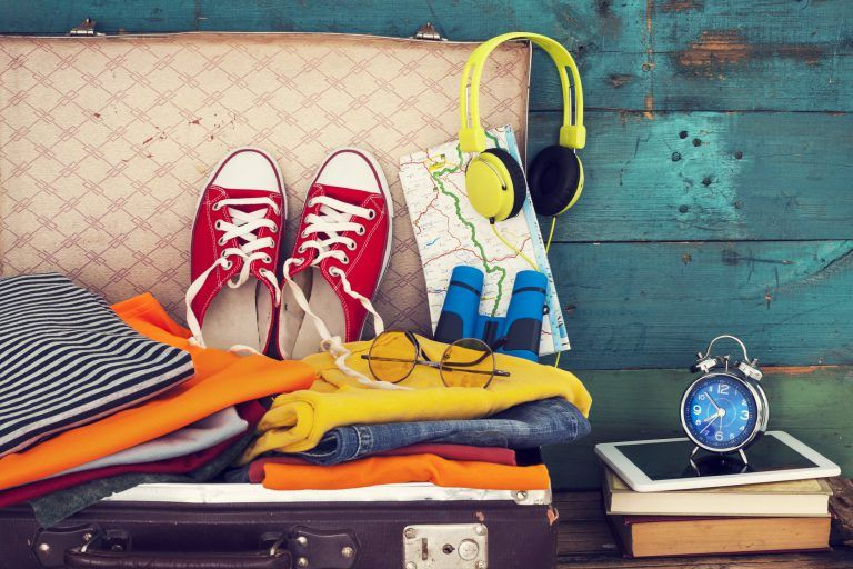 suitcase travel montage with clothes with converse and headphones