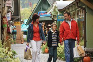 family of three with shopping bags walking through mall at gatlinburg, Tennessee, USA