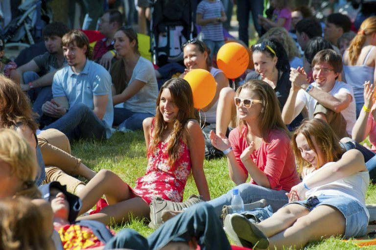 crowd of people sitting in the grass clapping at an outdoor festival
