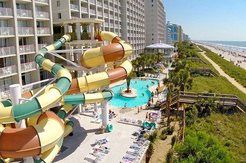 aerial drone view of waterslides and outdoor pool with beach in background at Crown Reef Beach Resort and Waterpark in Myrtle Beach, South Carolina, USA