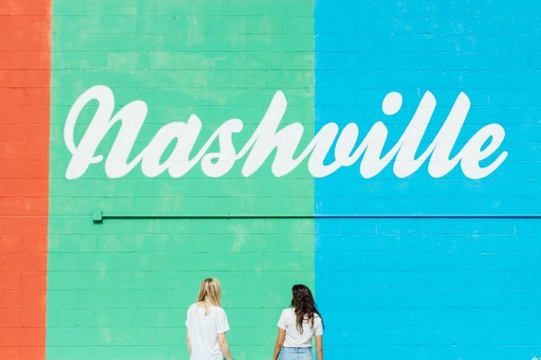 two women standing in front of nashville wall graffiti