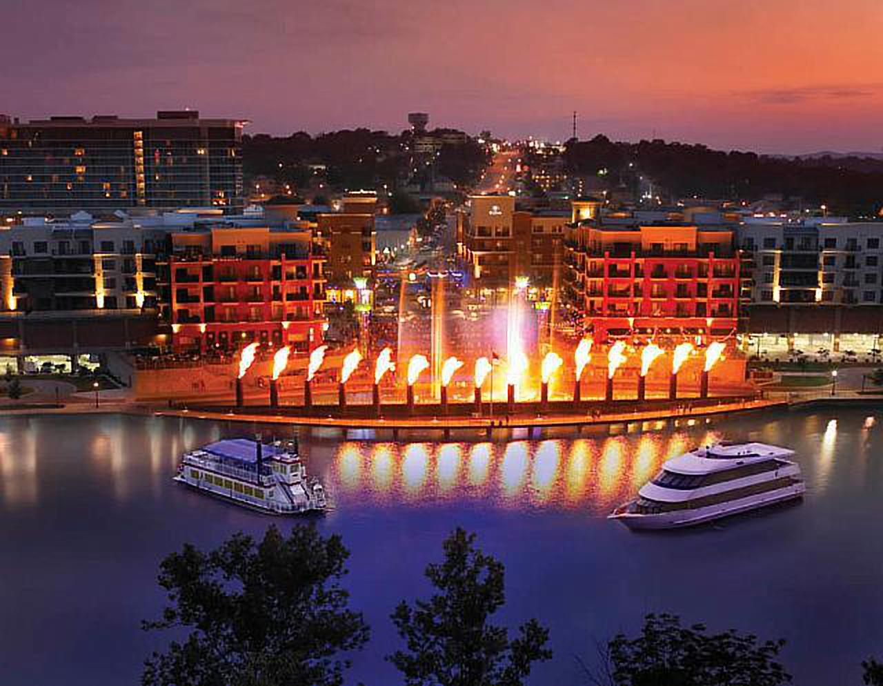 night view of the Fire and Ice show downtown at the Branson landing with boats parked on the water in front in Branson, Missouri, USA