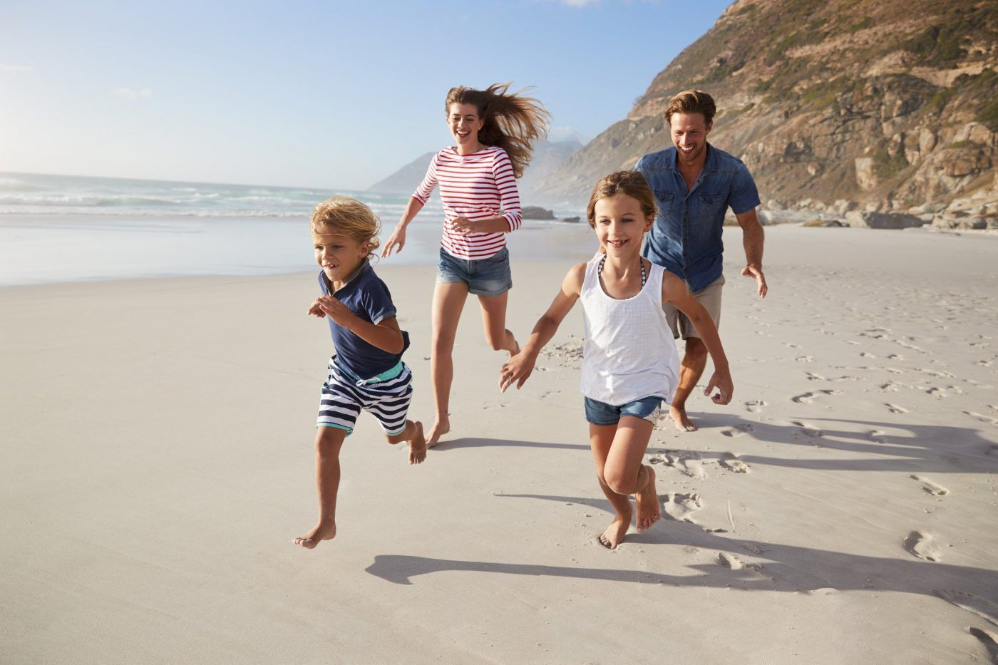 family running through sandy beach together during daytime