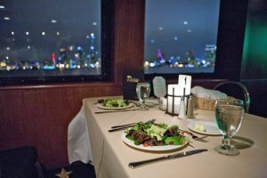 table set for dinner with outside view of water and skyline