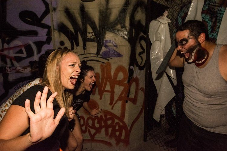 two women screaming at man in costume with knife at Halloween Horror Nights at Universal Studios in Orlando, Florida, USA