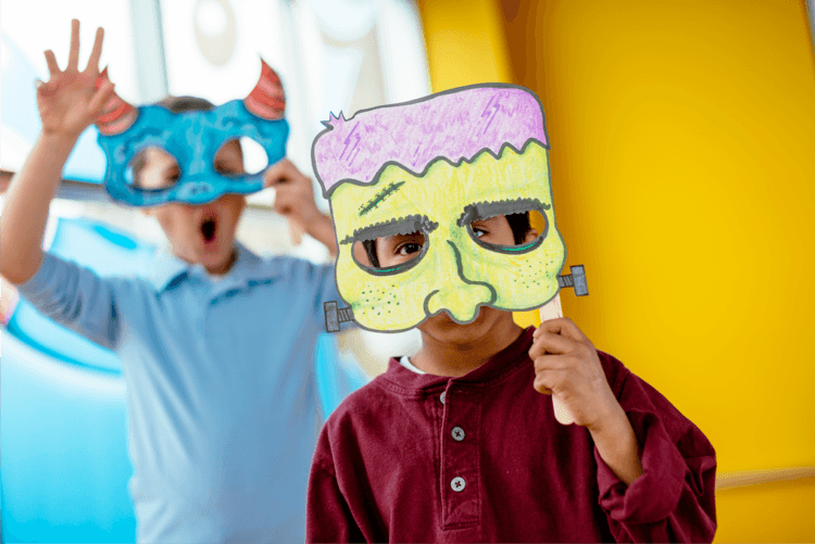 close up of two children holding up colored masks at Crayola Experience Orlando Screamin Green Hauntoween
